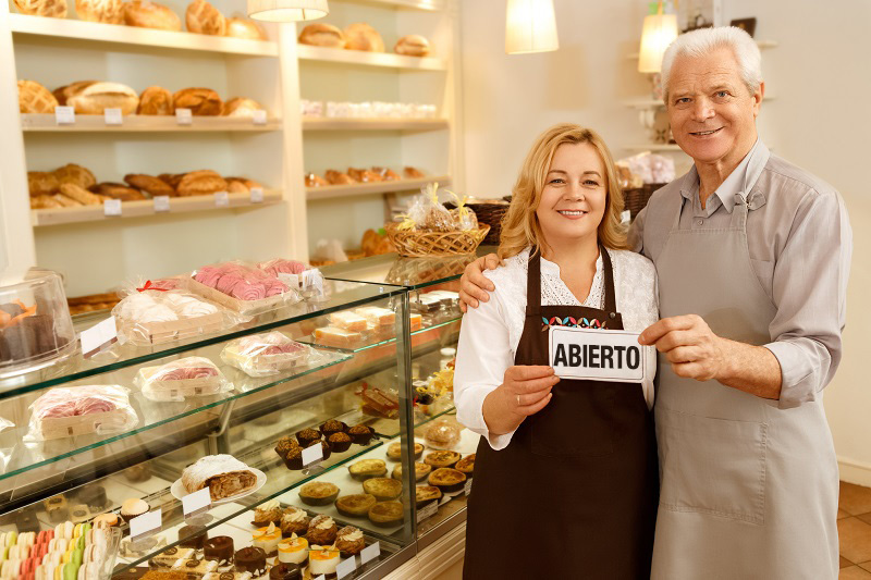 """Dos personas en una panadería con el cartel de """"ABIERTO"""""""